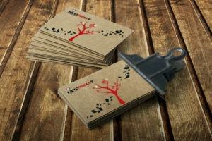 Επαγγελματικές κάρτες τυπωμένες σε ειδικό χαρτί με εξειδικευμένη διαδικασία εκτύπωσης πιασμένες με μεταλλικό ματαλάκι επάνω σε ξύλινη επιφάνεια.